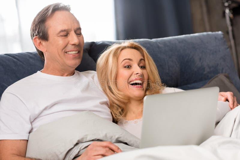 Mitt åldrades par genom att använda bärbara datorn och ligga på säng hemma arkivbilder