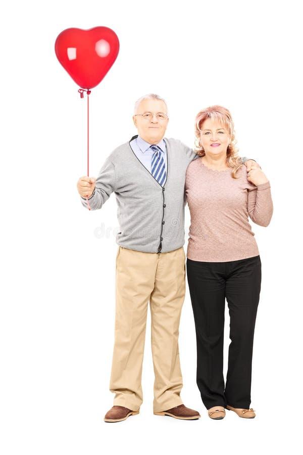 Mitt åldrades par i kramen som rymmer en röd hjärta, sväller royaltyfri foto
