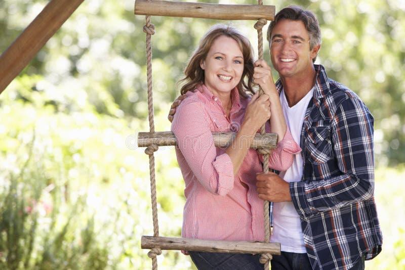 Mitt åldrades par i trädgård vid treehousen arkivfoton
