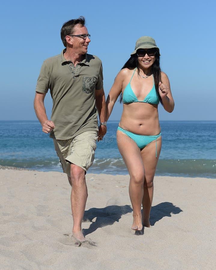 Mitt åldrades par på den sandiga stranden royaltyfri bild