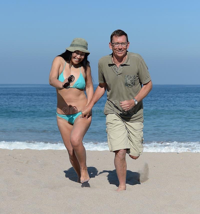 Mitt åldrades par på den sandiga stranden royaltyfri foto