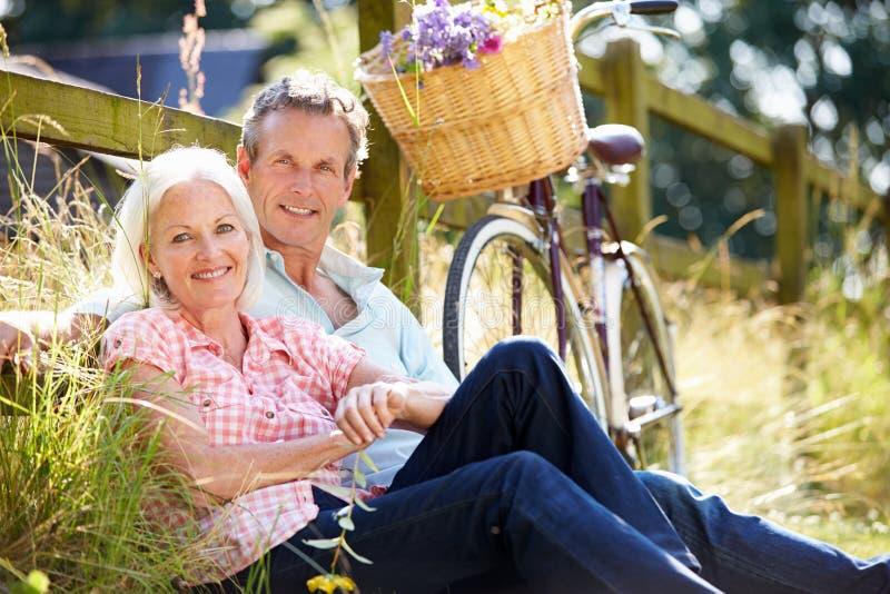 Mitt åldrades par som kopplar av på landscirkuleringsritt royaltyfria foton