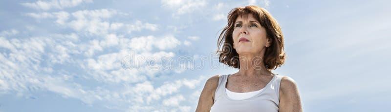 Mitt åldrades yogakvinnan som söker för jämvikt över sommarhimmel arkivfoto