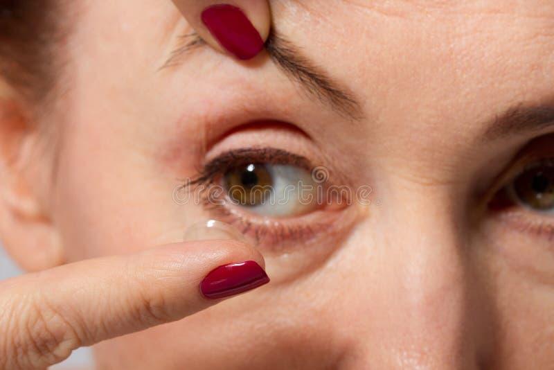 Mitt åldras kvinna med påsar under ögonen som sätter upp kontaktlinsen i hennes bruna öga, slut och makrosikt Medicin och vision royaltyfri fotografi