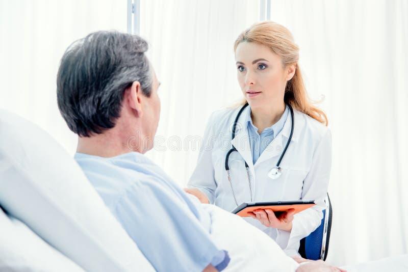 Mitt åldras patient som ligger på säng, doktor som använder den digitala minnestavlan och sitter nära honom arkivfoto