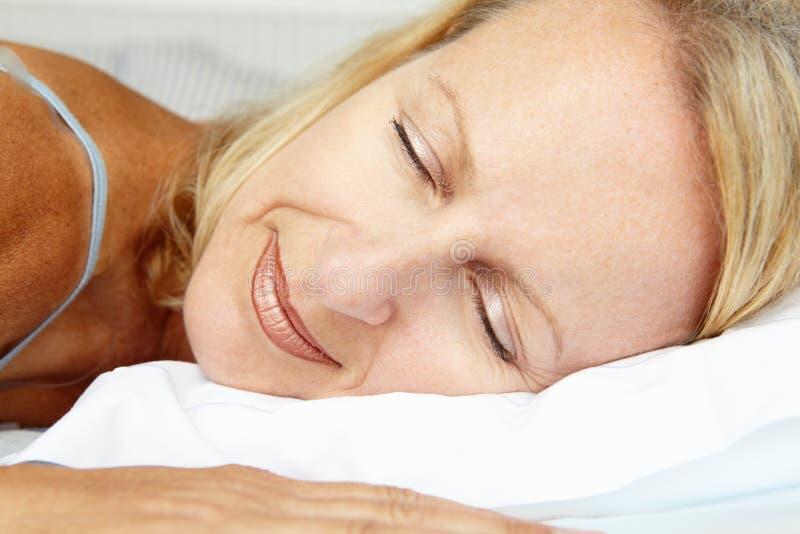 Mitt- åldriga kvinnor som ligger och sovar på ett underlag royaltyfri bild