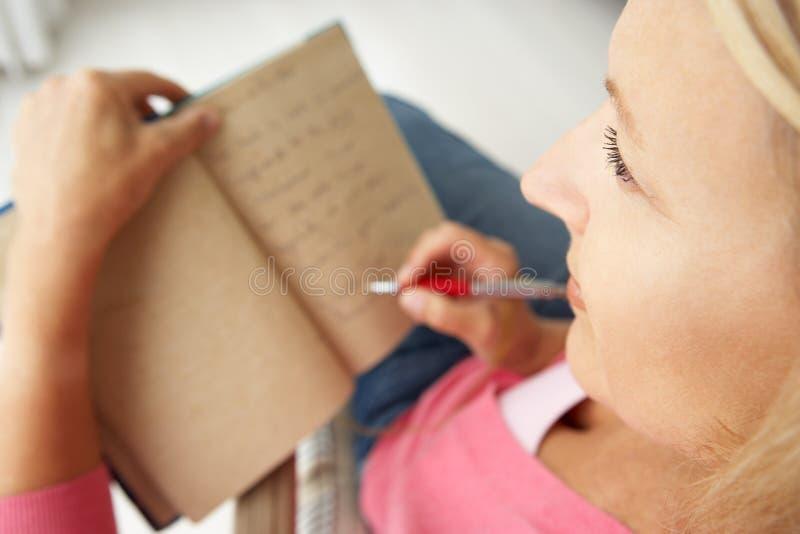 Mitt- åldriga kvinnor som skriver i anteckningsbok arkivbild