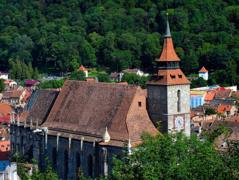Mitt av den gamla staden av den Brasov stadssvarta kyrkan Transilvania, Rumänien I bakgrund kan du se det Tampa berget 955 M arkivbild