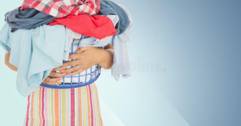 Mitt- avsnitt av den hållande korgen för kvinna som är full av kläder fotografering för bildbyråer