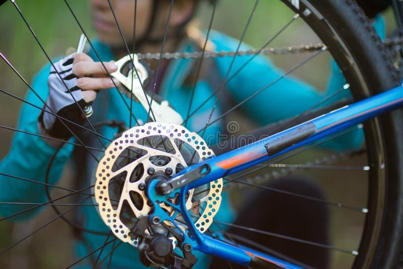 Mitt--avsnitt av den kvinnliga cyklisten som reparerar mountainbiket fotografering för bildbyråer