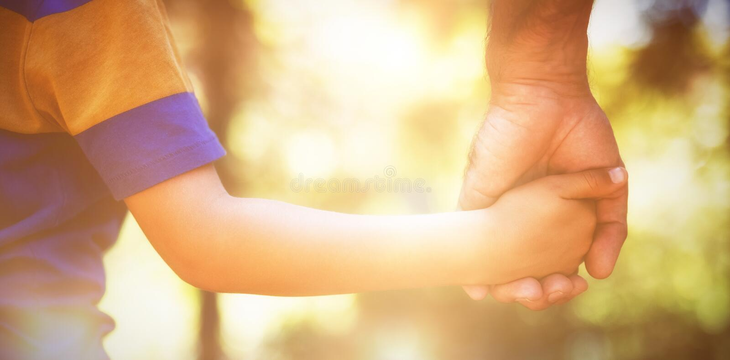 Mitt- avsnitt av handen för pojkeinnehavfäder arkivbild