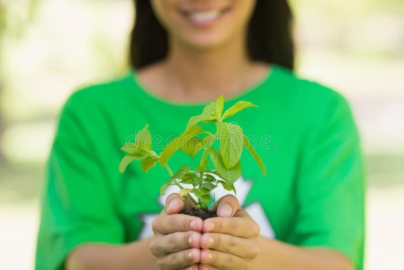 Mitt- avsnitt av kvinnan i återvinningt-skjortan som rymmer den unga växten arkivfoton