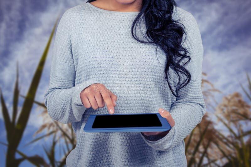 Mitt- avsnitt av kvinnan som använder den digitala minnestavlan mot fält royaltyfria foton