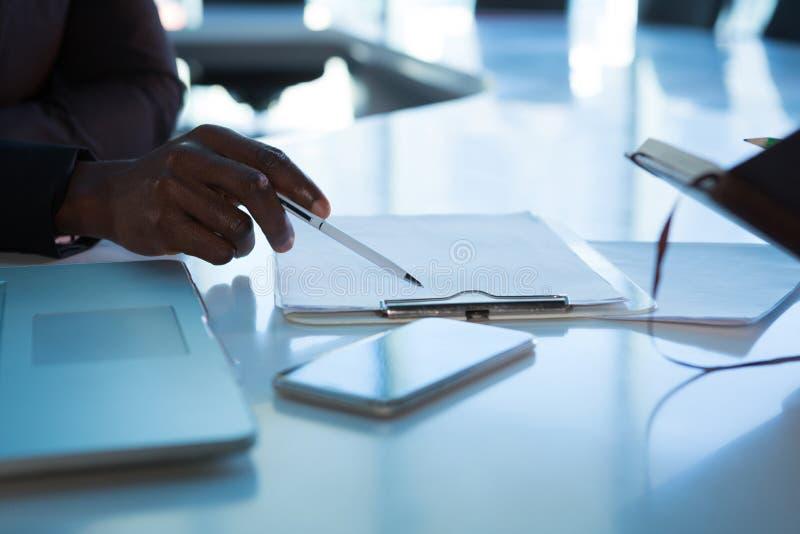Mitt- avsnitt av ledare som arbetar över skrivplattan på skrivbordet royaltyfria foton