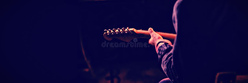 Mitt--avsnitt av mannen som spelar gitarren royaltyfri foto