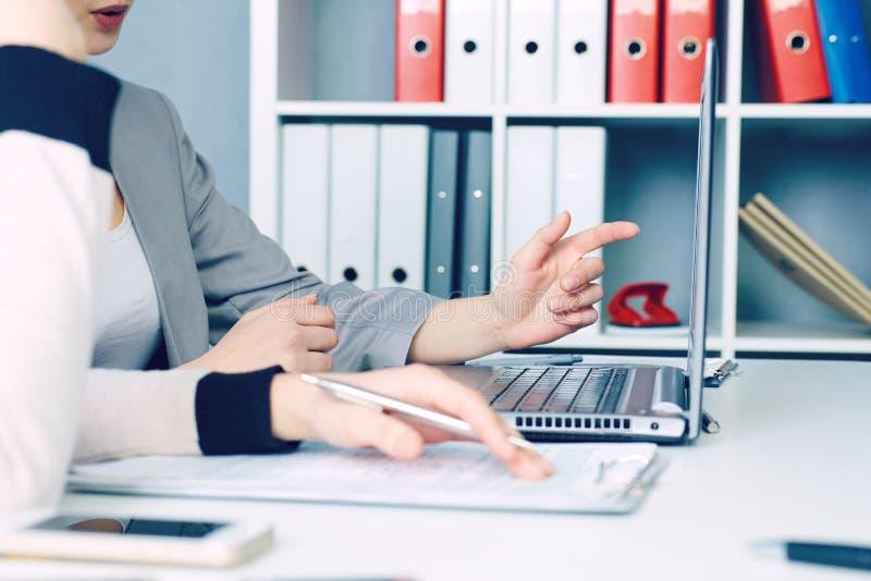 Mitt- avsnitt av två affärskvinnor som tillsammans sitter och arbetar på bärbara datorn Ledare som möter i en kontorslobby Kvinna royaltyfri fotografi