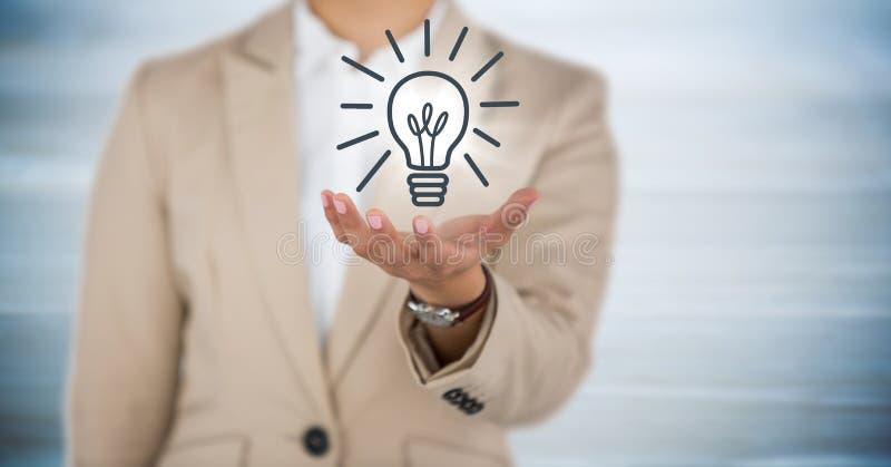 Mitt- avsnitt för affärskvinna med handen ut och lightbulbdiagram med signalljuset mot oskarpt blått trä p royaltyfria bilder