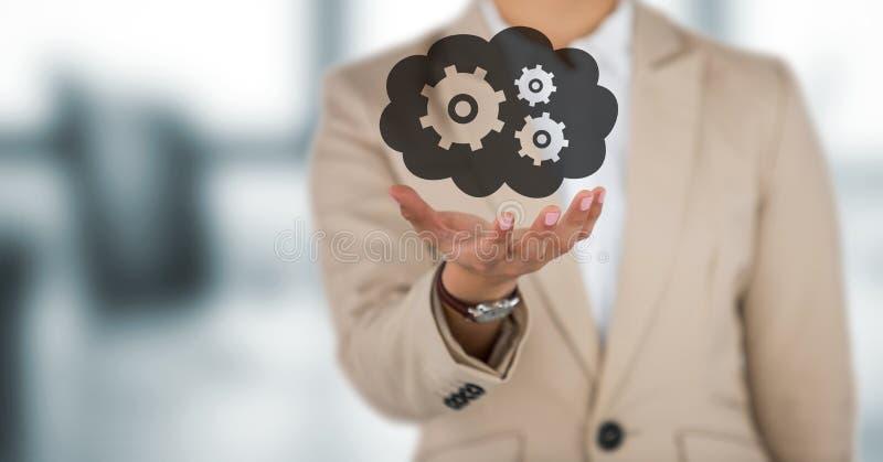 Mitt- avsnitt för affärskvinna med handen ut och molnet med kugghjul som är grafiska mot oskarpt grått kontor royaltyfria bilder