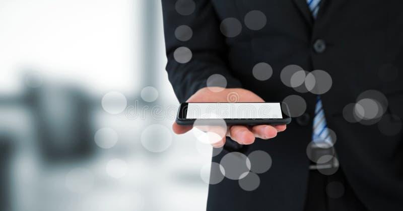 Mitt- avsnitt för affärsman med telefonen bak bokeh mot oskarpt grått kontor arkivbild