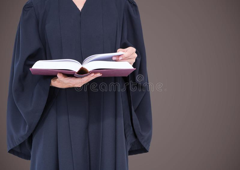 Mitt- avsnitt för kvinnlig domare med den öppna boken mot brun bakgrund royaltyfri foto