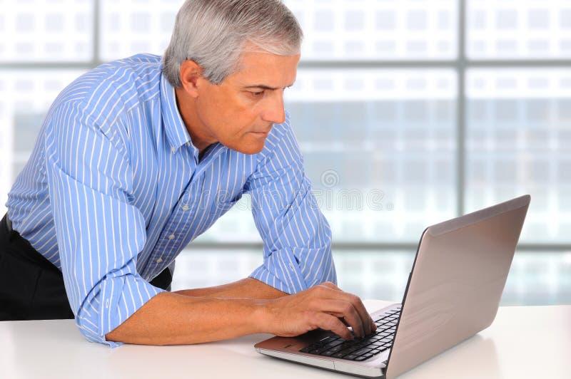 mitt för benägenhet för bärbar dator för ålderaffärsmanskrivbord arkivbild