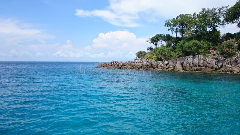 Mitt för blå himmel av havet och den lilla ön, royaltyfri bild