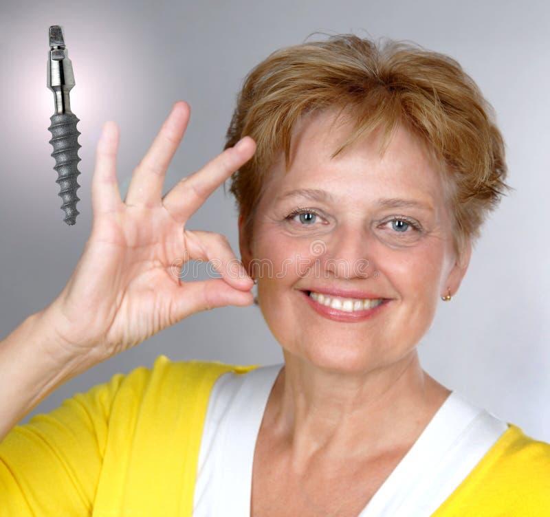 mitt- gammal tillfredsställd kvinna för åldrig implantat royaltyfri bild