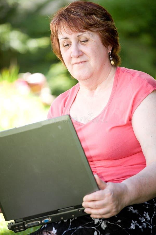 mitt- kvinna för ålderbärbar dator arkivbild
