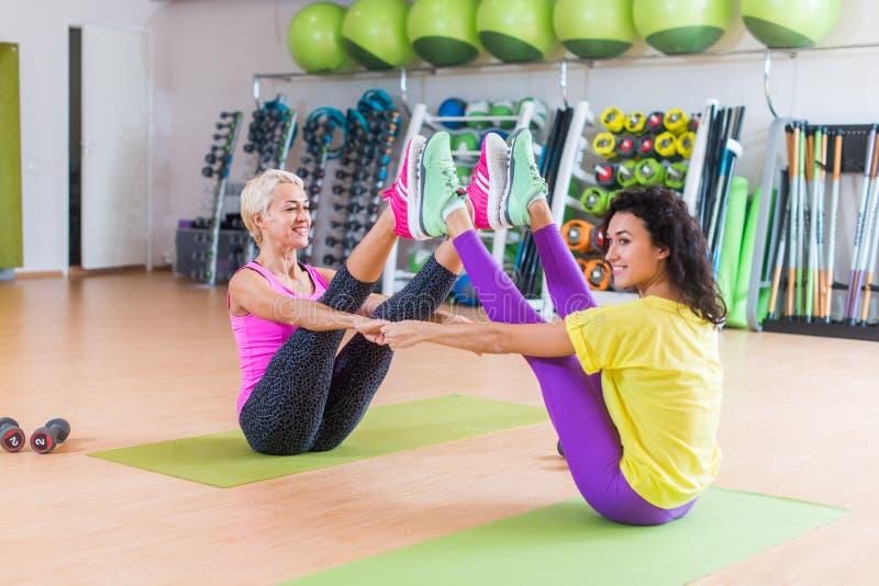 Mitt--?ldras kvinna som parvis utarbetar p? mats i en idrottshall i sportswearen som g?r yogakompisfartyget, posera med partnern arkivfoton