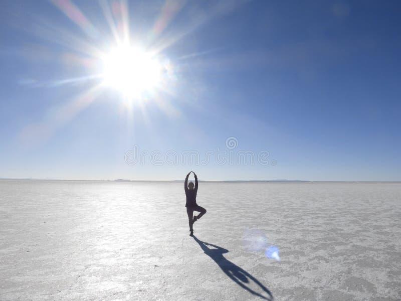 Mitt posera med solen på Uyuna de salta lägenheterna royaltyfria foton