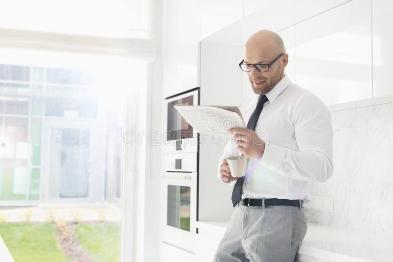 Mitt- vuxen affärsman som har kaffe, medan läsa tidningen hemma royaltyfri fotografi