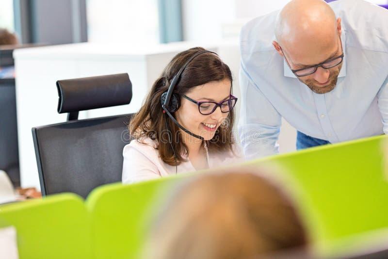 Download Mitt- Vuxen Affärsman Som I Regeringsställning Hjälper Den Kvinnliga Operatören Arkivfoto - Bild av kund, företags: 78728778