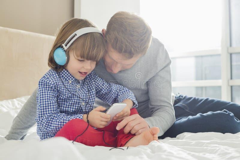 Mitt- vuxen fader med lyssnande musik för pojke på hörlurar i sovrum royaltyfria bilder