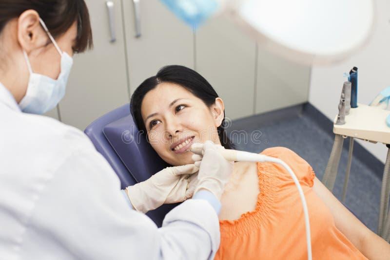 Mitt- vuxen kvinna på tandläkaren arkivbild