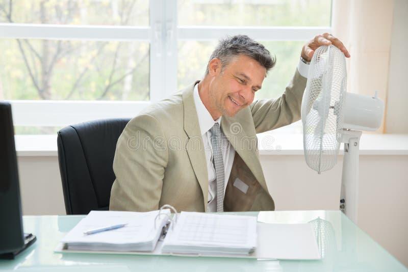 Mitt--vuxen människa affärsman som sitter nära fan royaltyfri foto