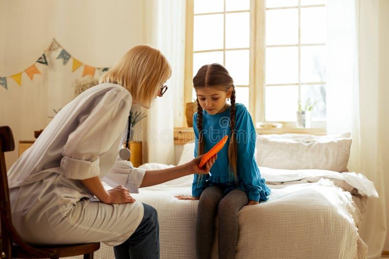 Mitt--vuxen människa läkare som visar en minnestavla till en söt liten flicka arkivbild