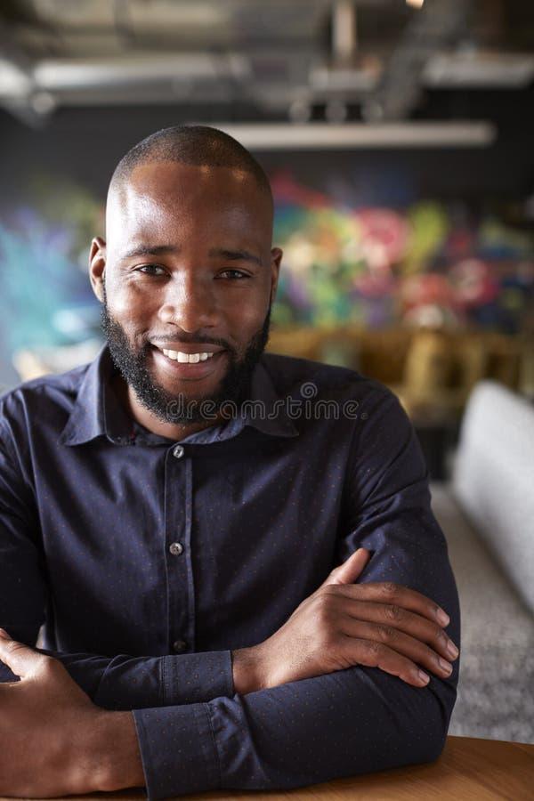 Mitt- vuxet svart manligt idérikt sammanträde på en tabell i ett kontorskafé som ler till kameran, slut upp, skörd arkivfoto