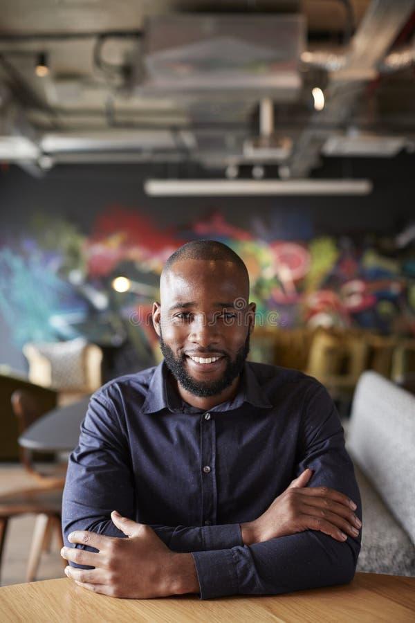 Mitt- vuxet svart manligt idérikt sammanträde på en tabell med armar korsade att le till kameran, slut upp royaltyfri bild