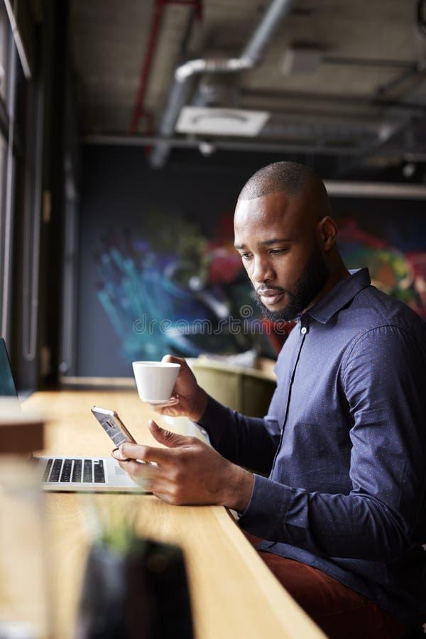 Mitt- vuxet svart manligt idérikt sammanträde vid fönstret som har kaffe genom att använda smartphonen, sidosikt, lodlinje arkivbilder