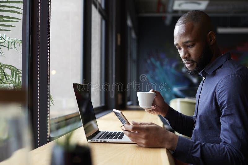 Mitt- vuxet svart manligt idérikt sitter vid fönstret som har kaffe, genom att använda en bärbar dator och en smartphone, sidosik royaltyfri bild