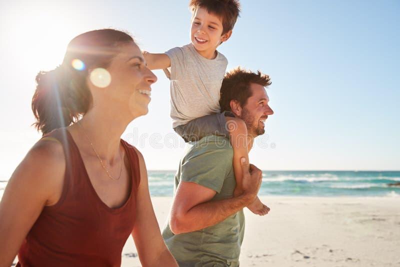 Mitt- vuxna vita par som går på en strand, bärande son för farsa på hans skuldror, slut upp, linssignalljus arkivfoton