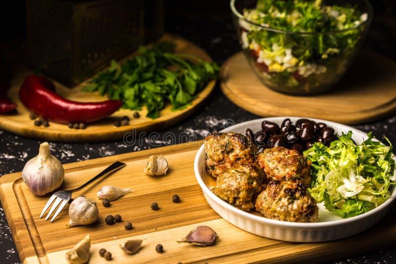 Mittagessen von Fleischkl?schen in der Tomatensauce, im Kopfsalat und in den schwarzen Bohnen stockfotos