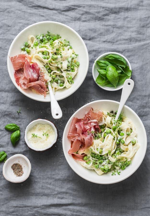 Mittagessentabelle in der Mittelmeerart Fettuccineteigwaren mit sahniger Soße, grünen Erbsen und Prosciutto auf grauem Hintergrun stockfotografie