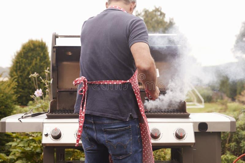 Mitte alterte brennendes Lebensmittel des Mannes auf einem Grill, hintere Ansicht stockbild