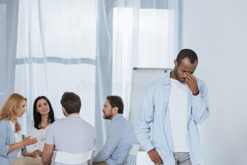 Mitte alterte den Afroamerikaner, der während die Leute betet, die hinten während sitzen lizenzfreie stockfotos