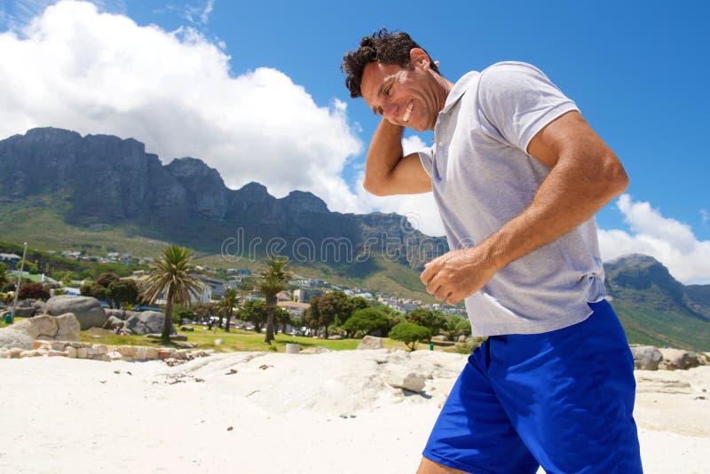 Mitte alterte den Mann, der auf den Strand im Sommer geht stockbilder