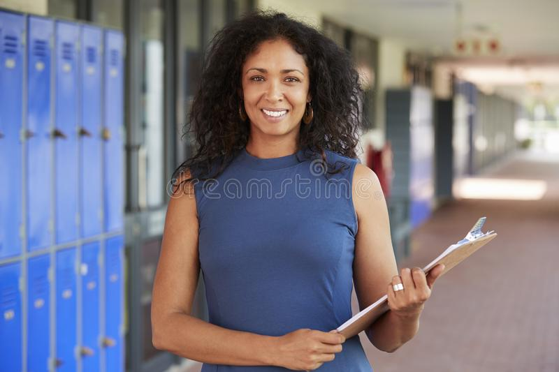 Mitte alterte den schwarzen weiblichen Lehrer, der im Schulkorridor lächelt lizenzfreies stockbild