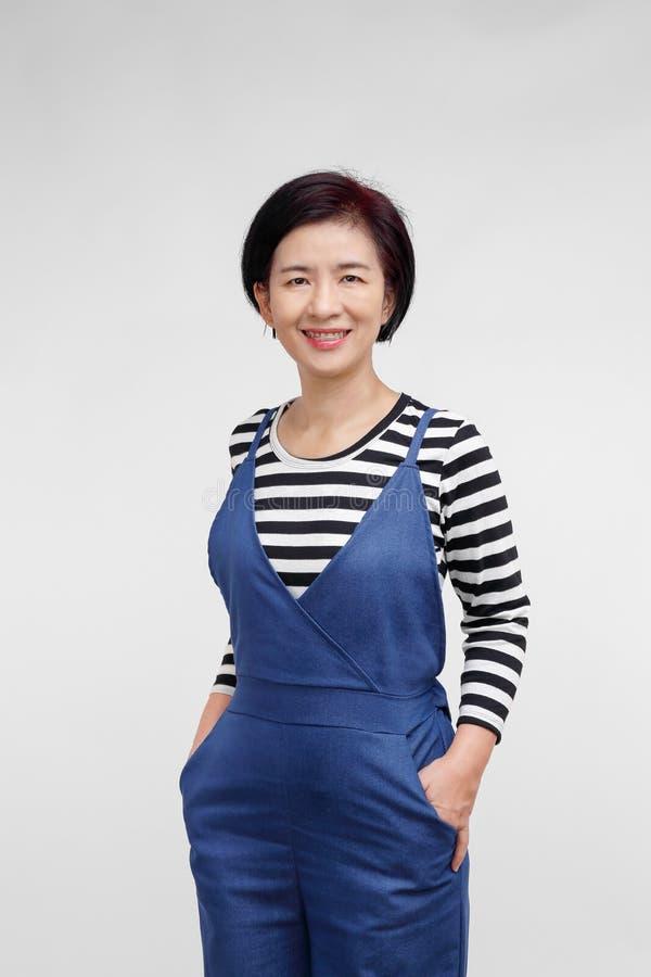 Mitte alterte die asiatische Frau, die in der zufälligen Kleidung lächelt stockbild