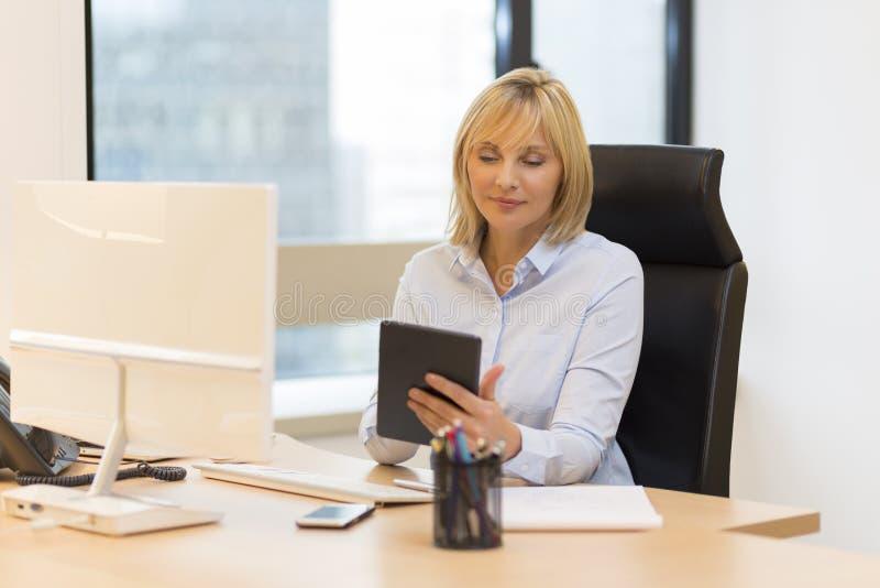 Mitte alterte die Geschäftsfrau, die Tabletten-PC im Büro verwendet stockbild