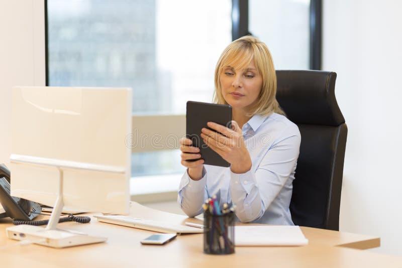 Mitte alterte die Geschäftsfrau, die Tabletten-PC im Büro verwendet lizenzfreie stockfotografie